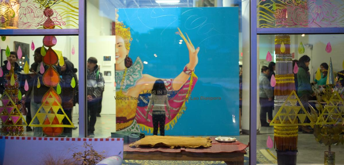 Behind a large window, there is a child looking at a mural depicting a traditional Lao dancer in front of a blue background. Surrounding the child are many other people in the gallery looking at artwork. - Laos In The House - Exhibition - Opening Reception