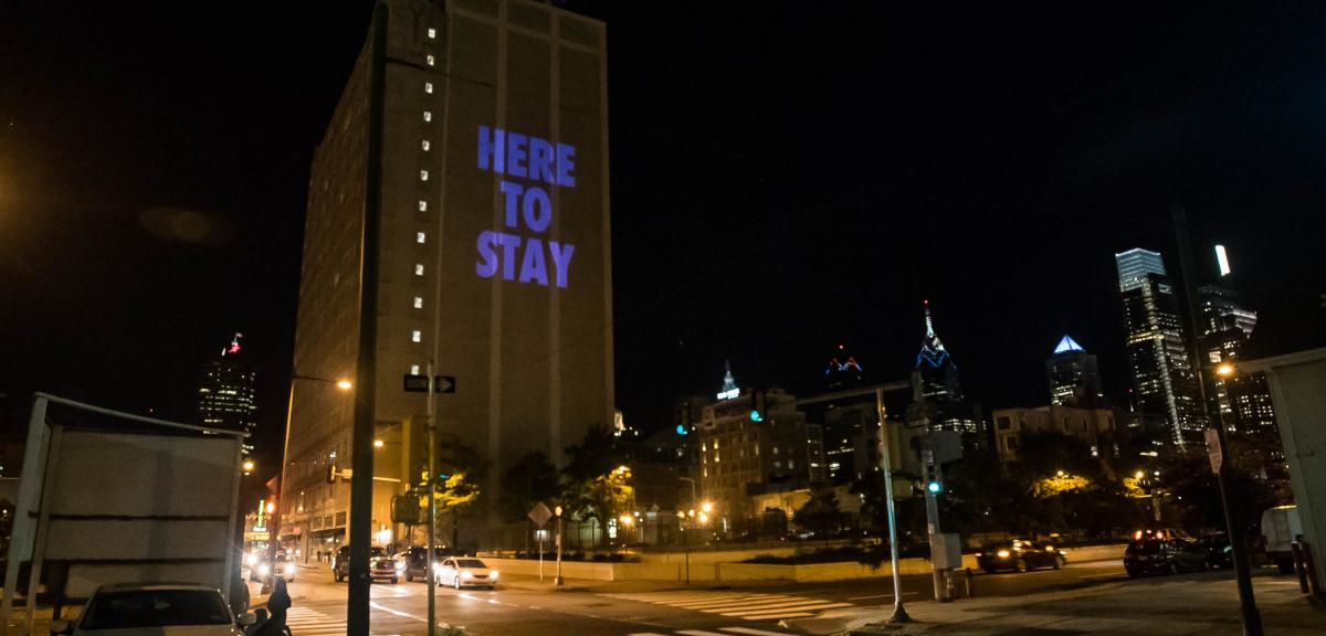 "Project of the phrase ""here to stay"" on a nighttime skyline"
