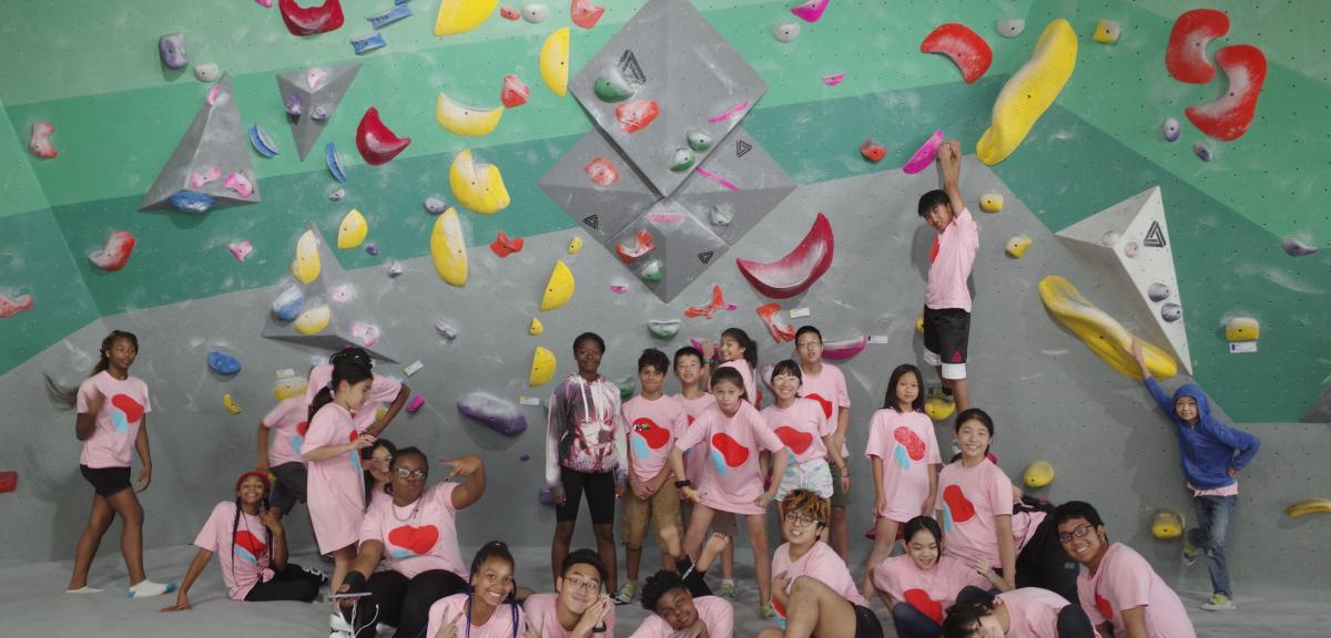 large group of kids in matching shirts at a rockclimbing gym