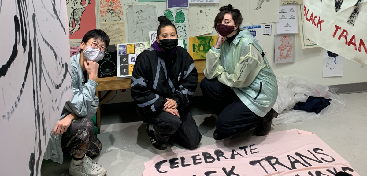 "The Fortune team kneels on the ground on front of a wall adorned in colorful flyers and posters exhibiting queer art. Two banners painted by Jeffrey Cheung flank them on either side. Foregrounding the team is a banner on the ground, painted with the words ""Celebrate BLACK TRANS LIVES ALWAYS"""