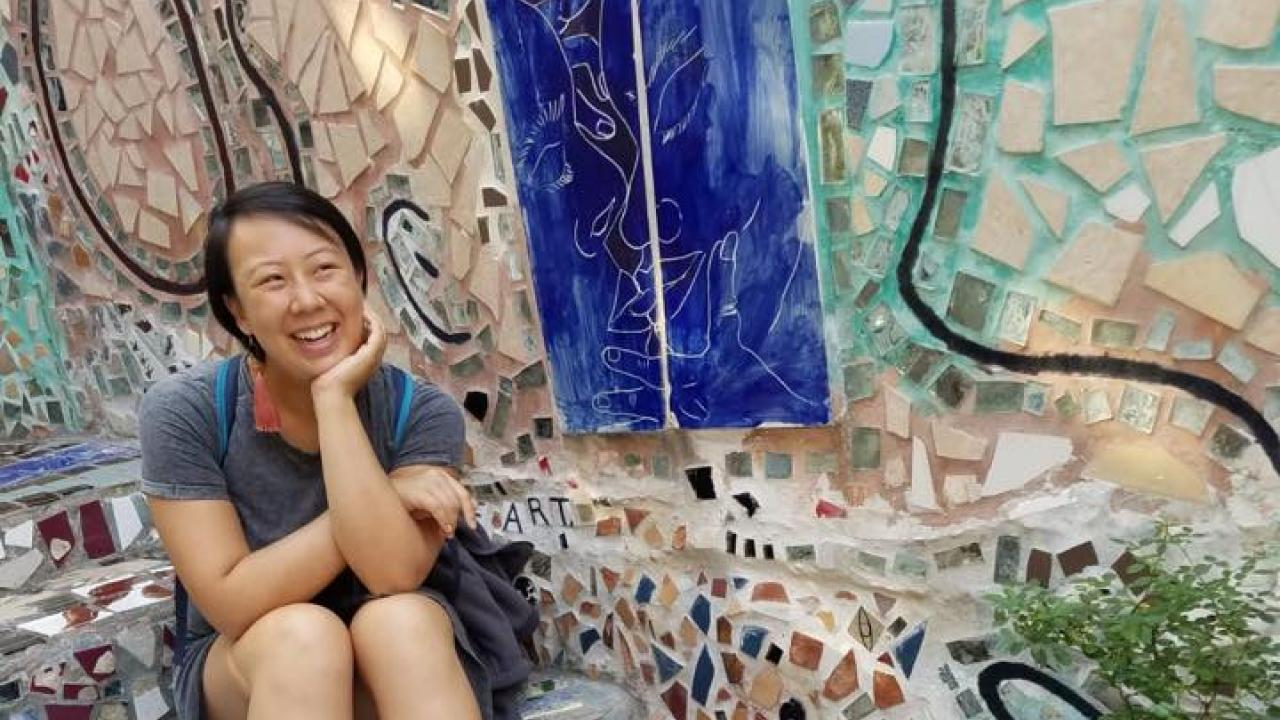 Francxs Gufan Nan smiling, sitting on the steps of an Isaiah Zagar mosaic