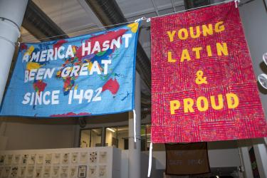 "Flags hanging in an open gallery space. One has a world map and reads ""America hasn't been great since 1492"" and the other ""Young Latin & Proud"""