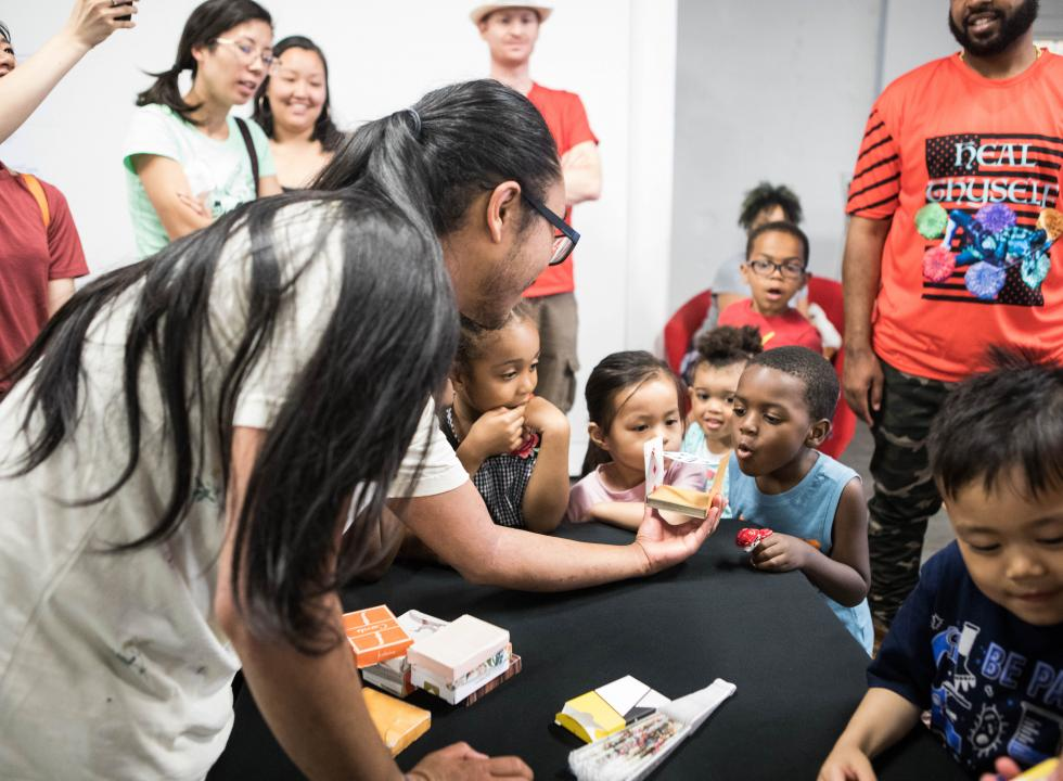 diverse crowd of amazed children gather around a magician doing card tricks