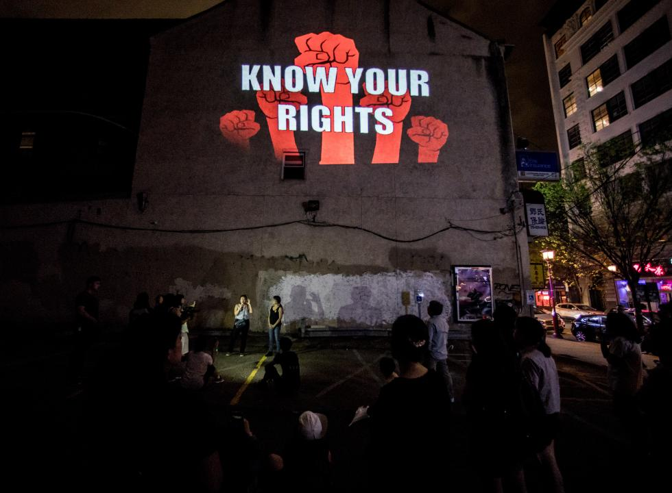 "Here To Stay by Chinatown Art Brigade - projection on the side of a building - red fists with the words ""KNOW YOUR RIGHTS"""