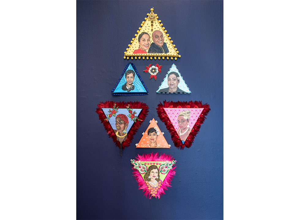 Eight flat colorful triangular sculptures with portraits painted on them are mounted on a dark blue wall - Jaishri Abichandani - Jasmine Blooms At Night