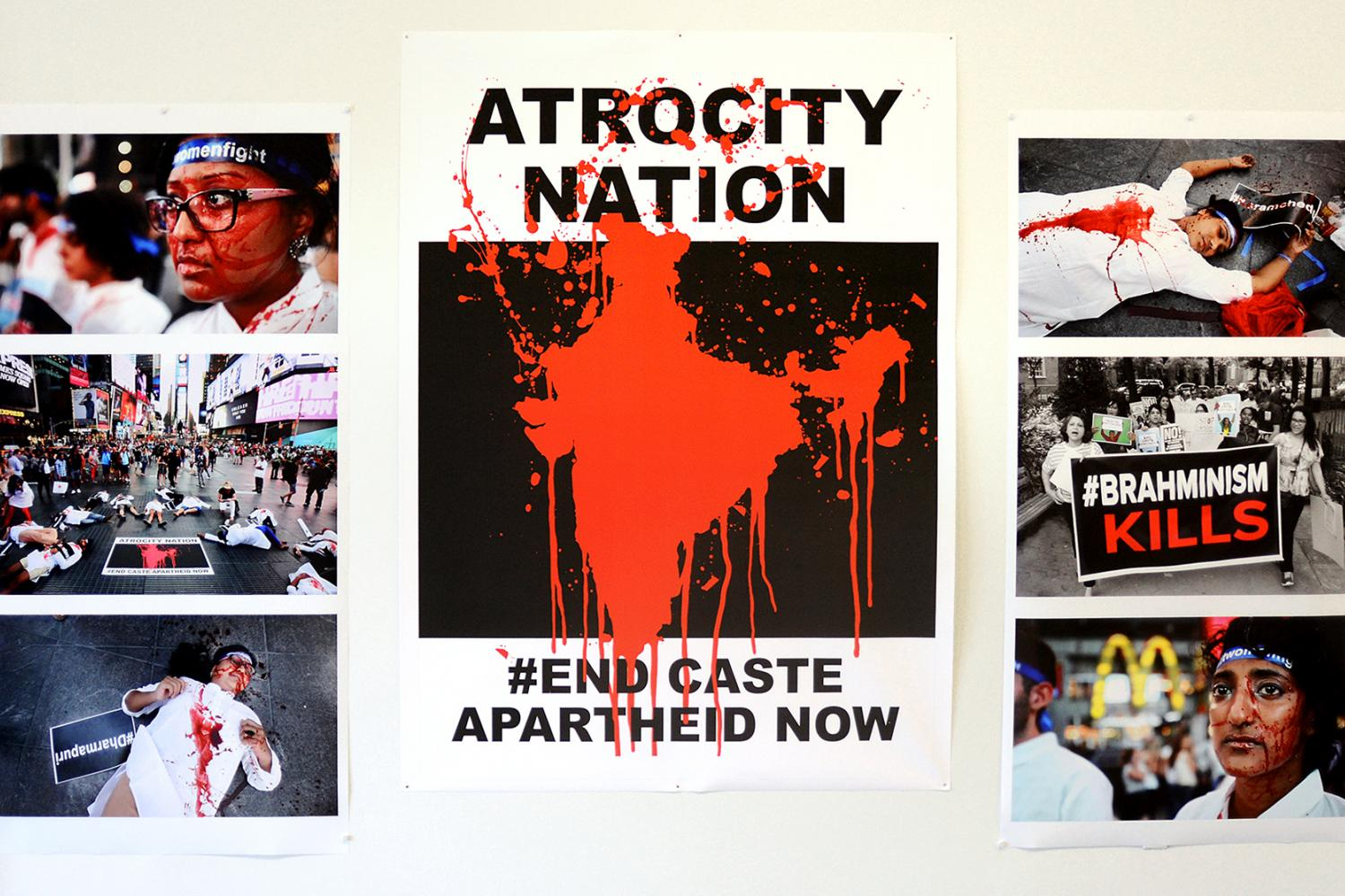 "A set of 3 posters on a white wall. The center poster depicts a red bloodstain in the shape of India over a black background. Along the top, the text says ""ATROCITY NATION"" and along the bottom the text says ""#END CASTE APARTHEID NOW"". On the left and right are posters depicting people at a protest wearing white and covered in fake blood. - Equality Labs - Atrocity Nation - Protest art demonstration"
