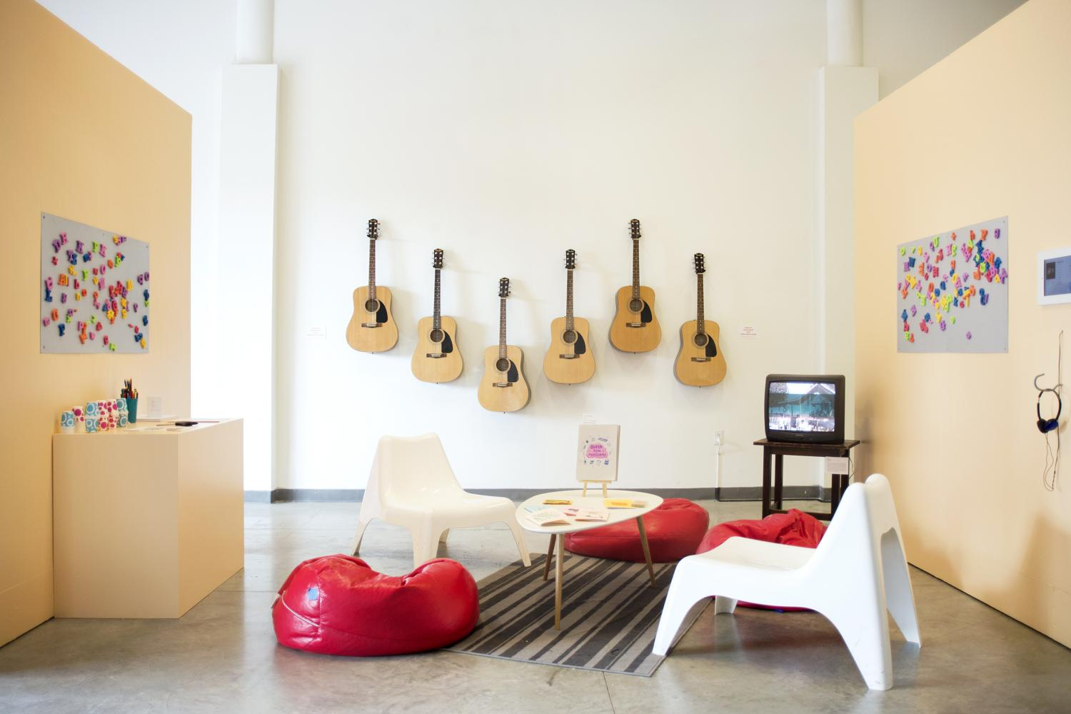 Between two yellow walls there is a living room setup consisting of a white coffee table situated on a dark grey rug and surrounded by red beanbag chairs and white plastic chairs. In the corner is a small TV on top of a wooden end table. In the background there are six guitars mounted on the white wall. The yellow walls have steel sheets mounted on them. On the steel sheets are colorful foam alphabet magnets. - The Beat of Resistance exhibition