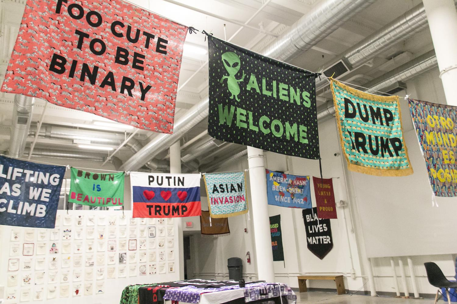 "Those Who Talk Back exhibition - Protest banners hanging across a room with text reading ""Too cute to be binary"", ""Aliens Welcome"", ""Dump Trump"", among others."