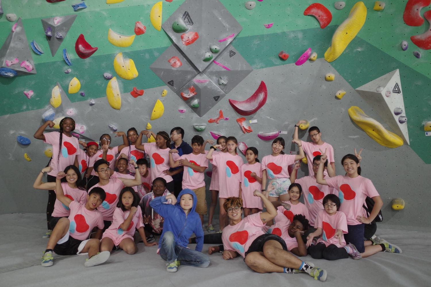 YAW Summer Program takes a group photo in front of a rock climbing wall, smiling with biceps flexed!