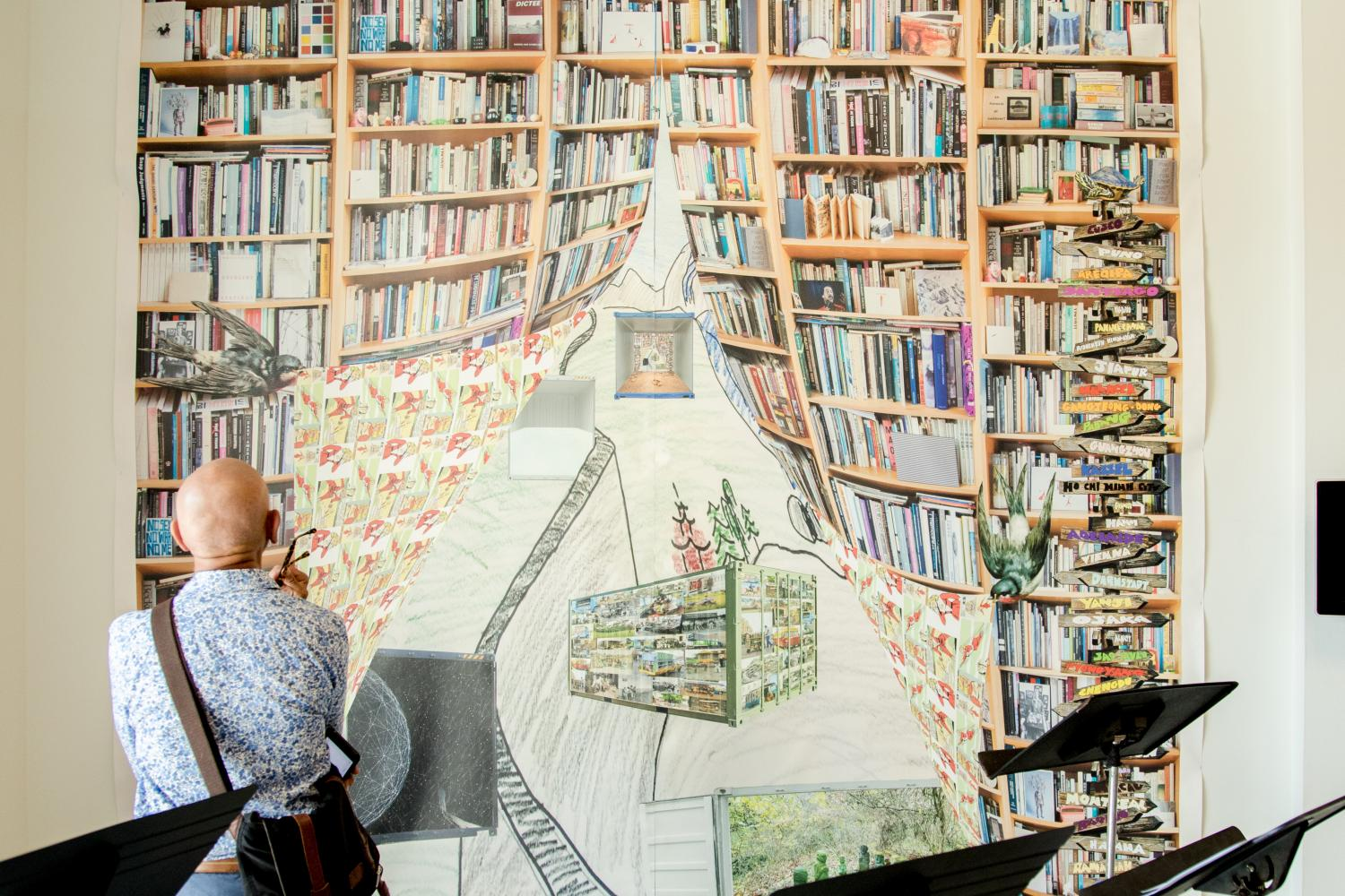 Man looks at a painting of bookshelves illustrated as a drawn curtains revealing a garden