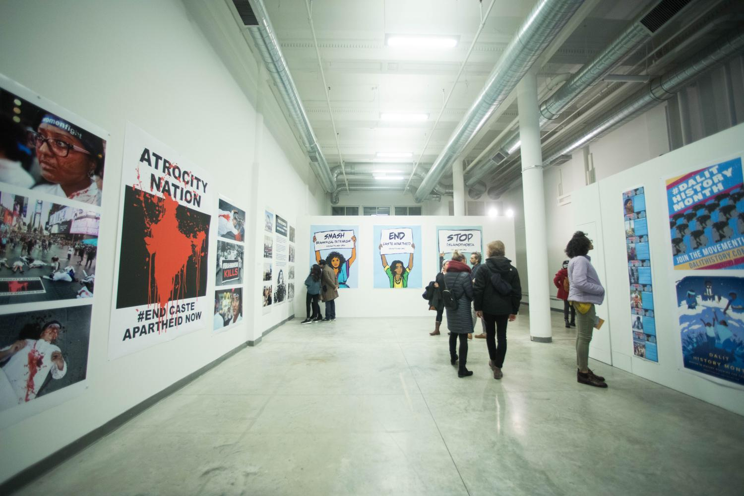 Image of open gallery space with posters on the walls and 6 visitors viewing artwork.
