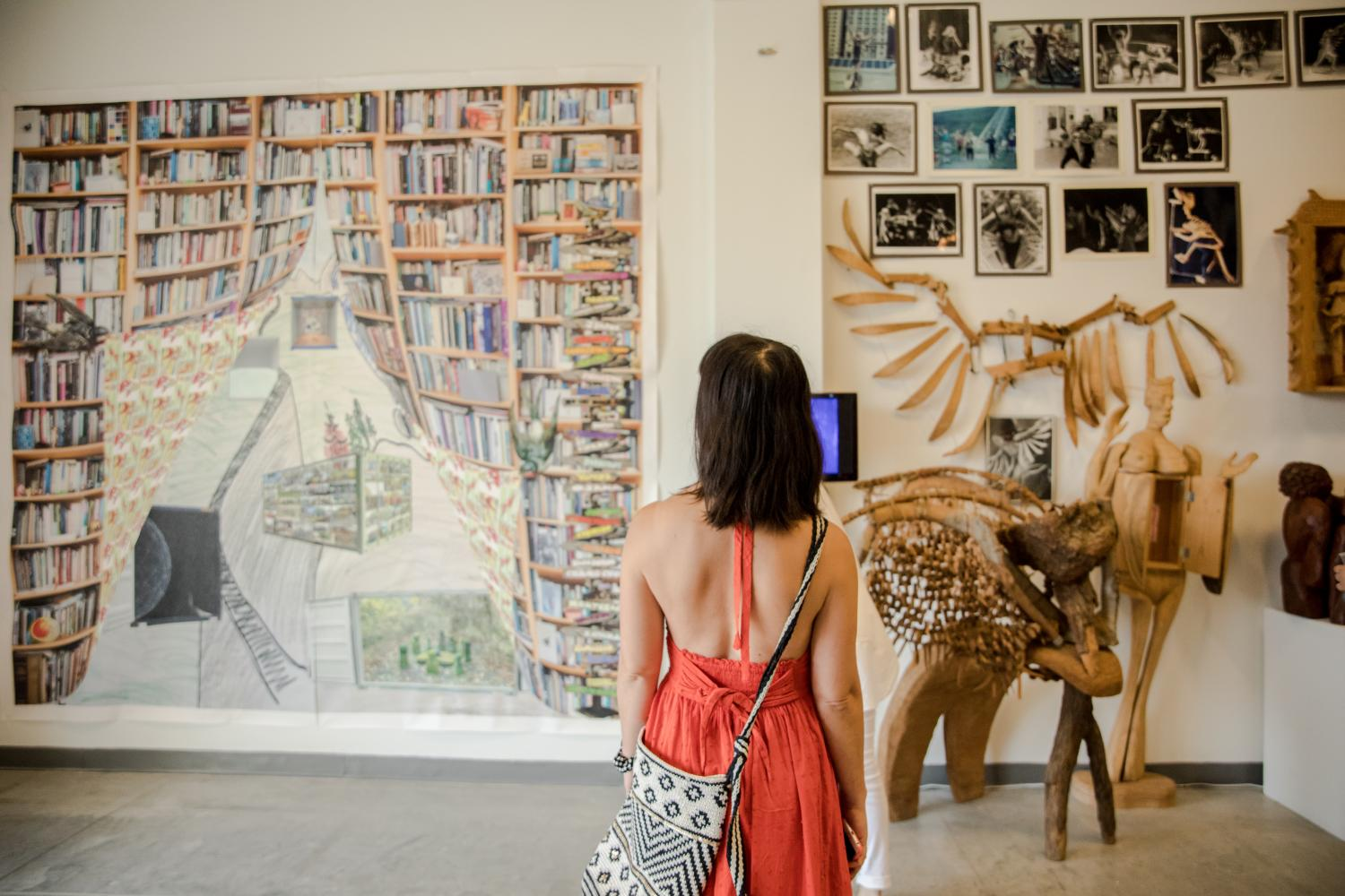 Person looking at artwork. On the right side is a large colorful print, on the left side is an installation of photographs and wooden sculptures.