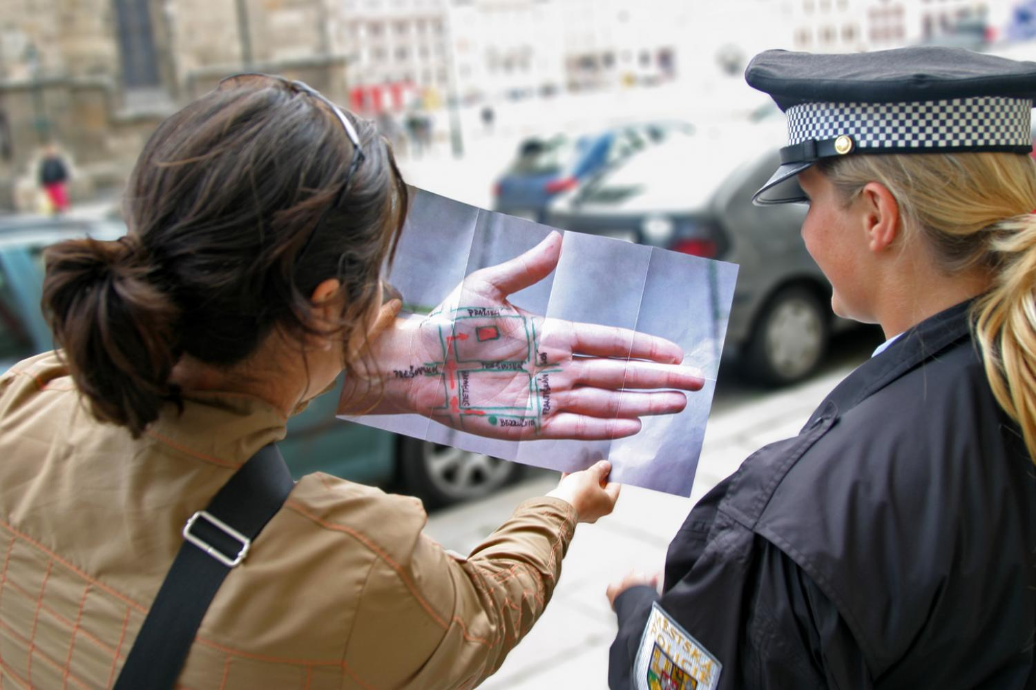 Two people looking at a large photo of a hand with a map drawn on it. - Yumi Janairo Roth - Meta Mapa (Czech Republic)