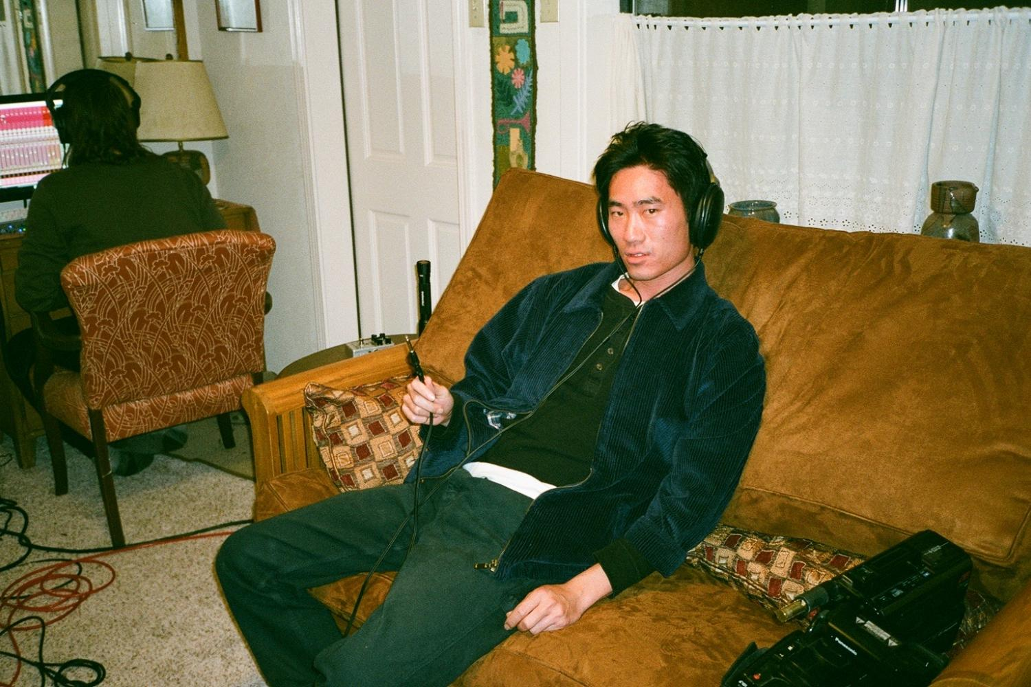 Diagonal shot of Alex Shen sitting on an old couch wearing headphones