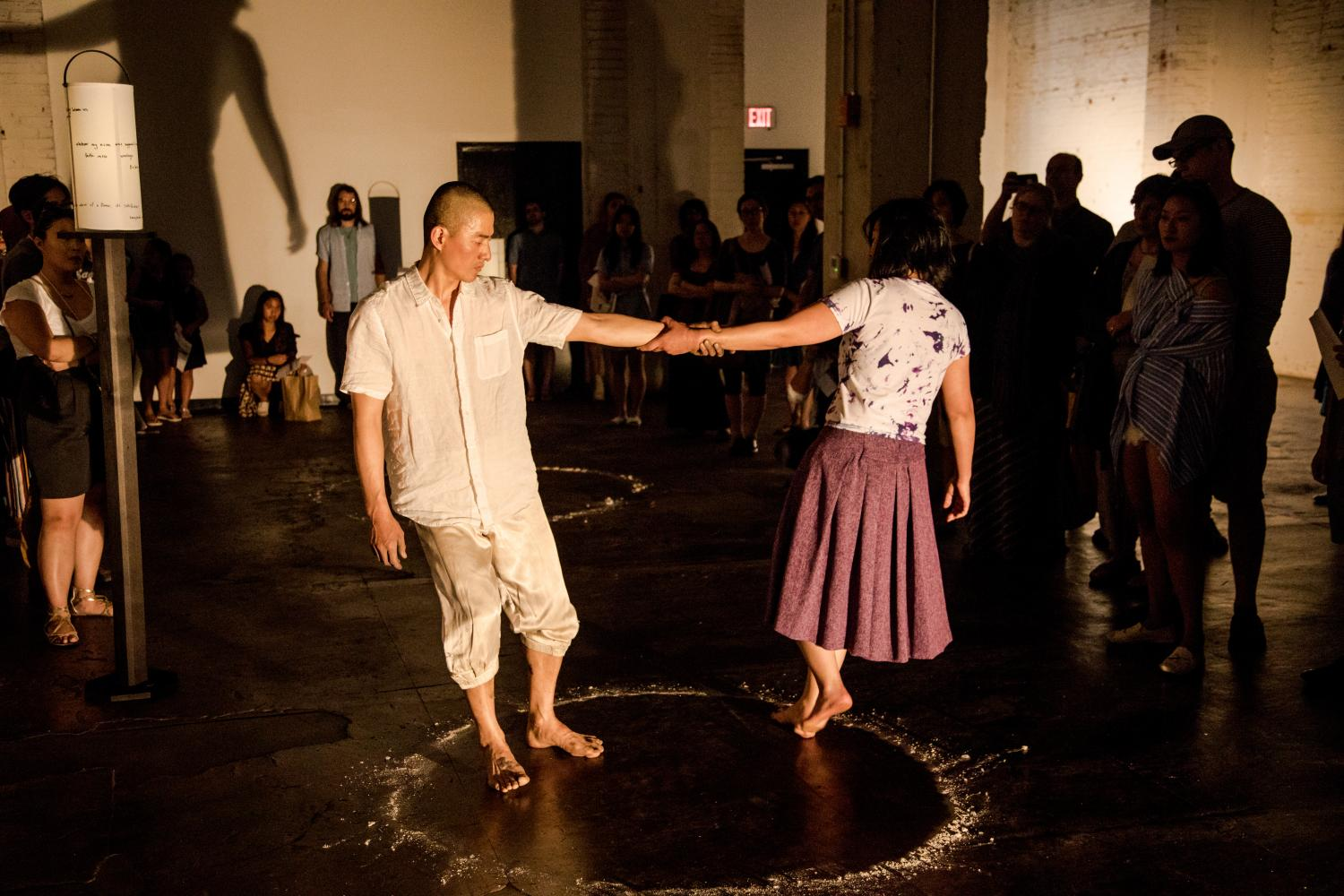 Two dancers within a circle of salt holding each other's right arms. Behind them is a crowd of audience members watching. They are in a dimply lit warehouse space. - (ex)CHANGE - Peace Light performance - Juliette Sueyeun Lee with Jungwoong Kim
