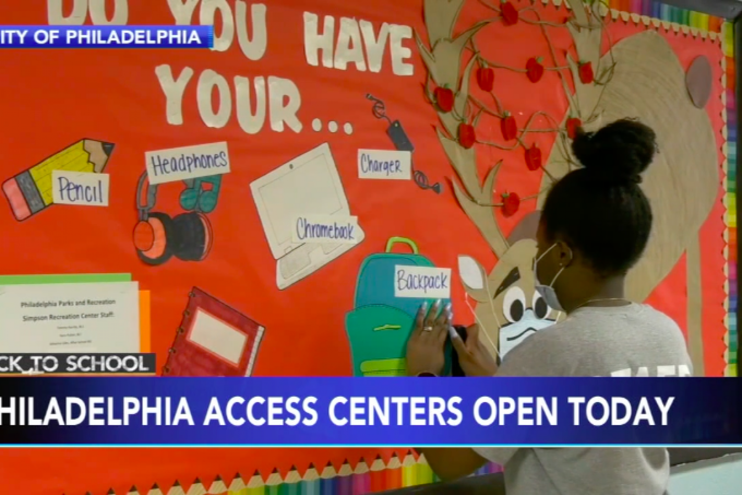"An access center staff person puts together a poster board welcoming students, a headline reads: ""Philadelphia Access Centers Open Today"""