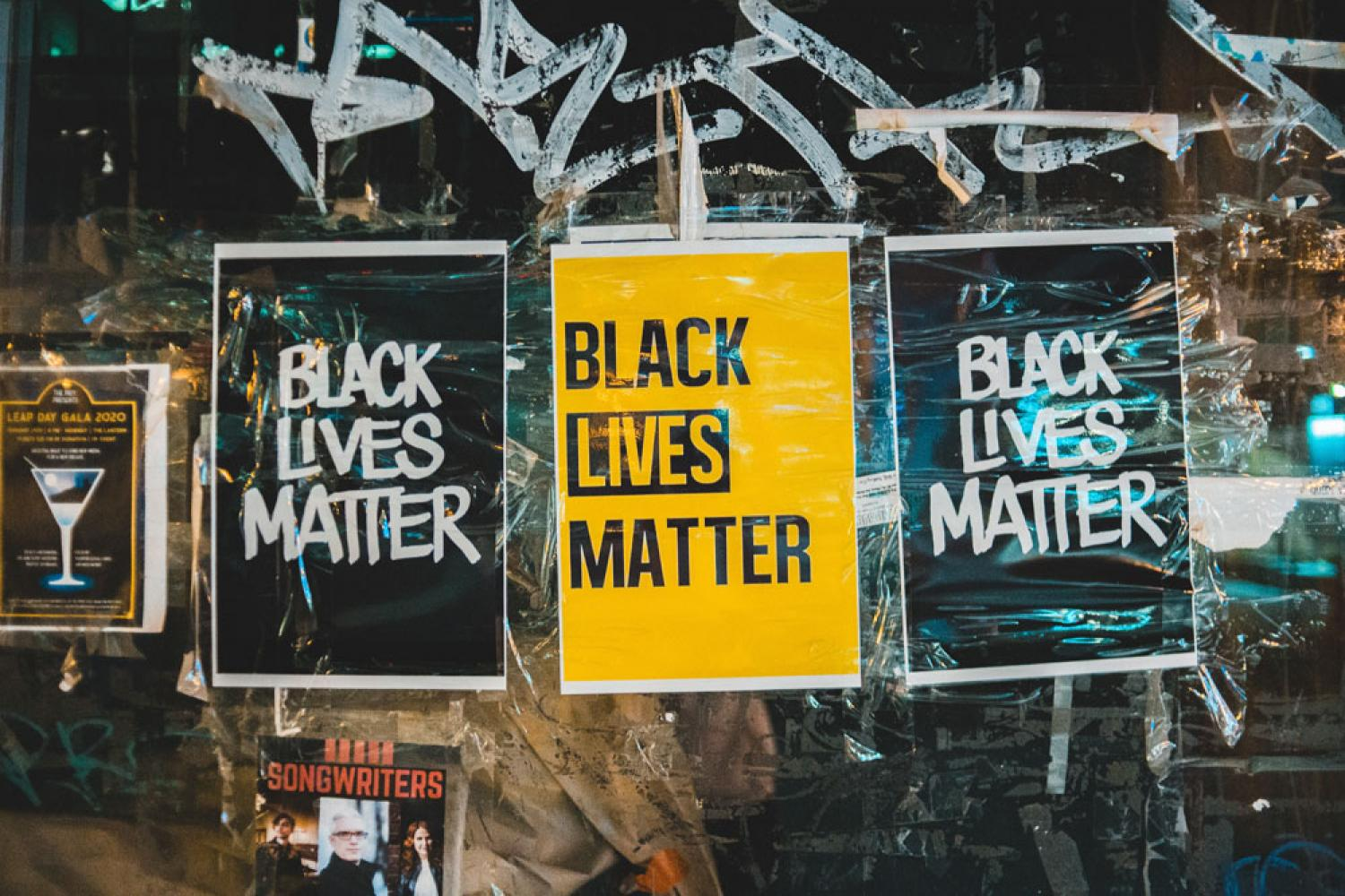 Photo by Erik Mclean from Pexels. Image of three banners, from right to left, Black banner that reads Black Lives Matter, center banner is yellow and reads Black Lives Matter, and the right banner is black and reads Black Lives Matter.