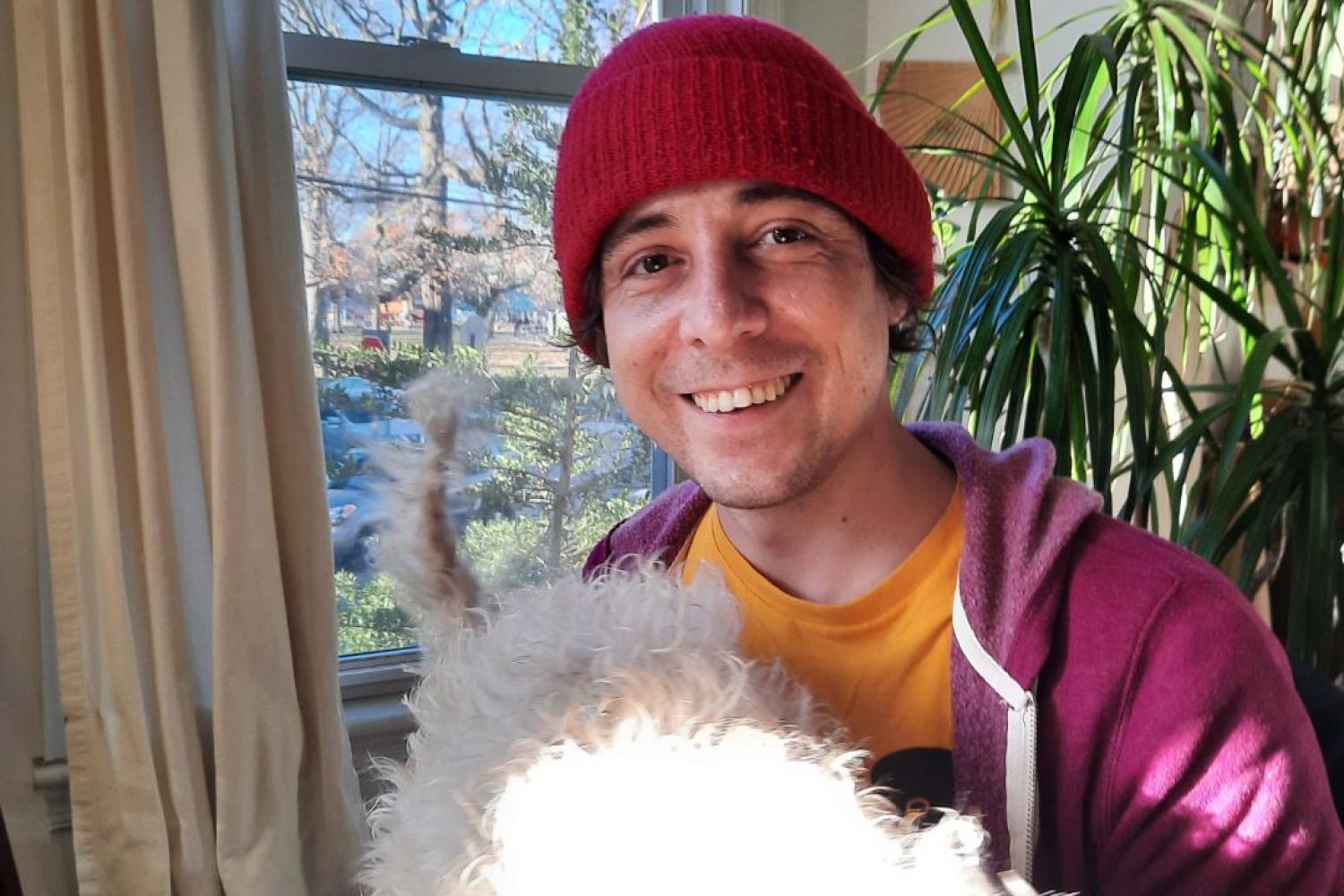 Alan Chelak smiling and wearing a knit cap, with his fluffy white dog on his lap in a sunlit room full of plants