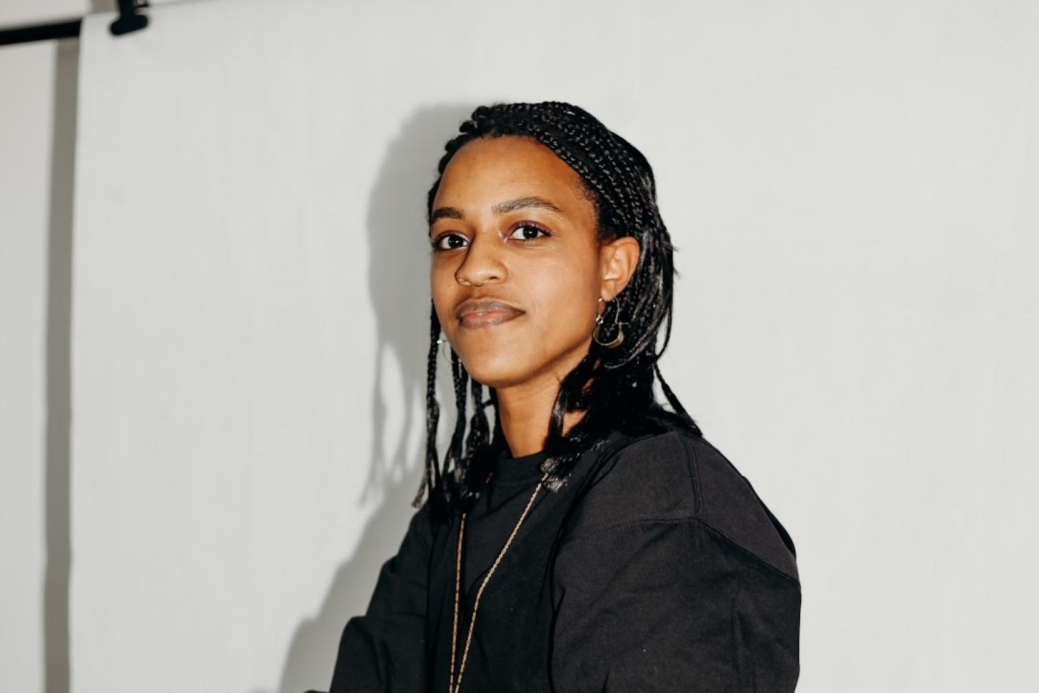 Artist Felicia Blow sits on a white chair in an all-white room, legs crossed and arms resting atop her legs. She wears a black bomber and black wide legged cropped pants with gold jewelry, and she smiles subtly at the camera, her braids tucked behind her ears.