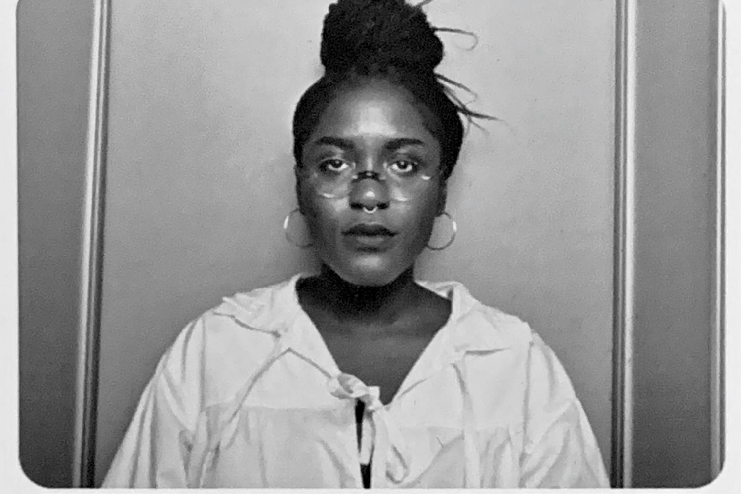 A black and white image of artist Soleil Summer, as she stares directly into the camera, wearing hoop earrings, wire rim round glasses, and white billowy shirt tied loosely at the collar. Her hair is up in a bun, she her expression is neutral.