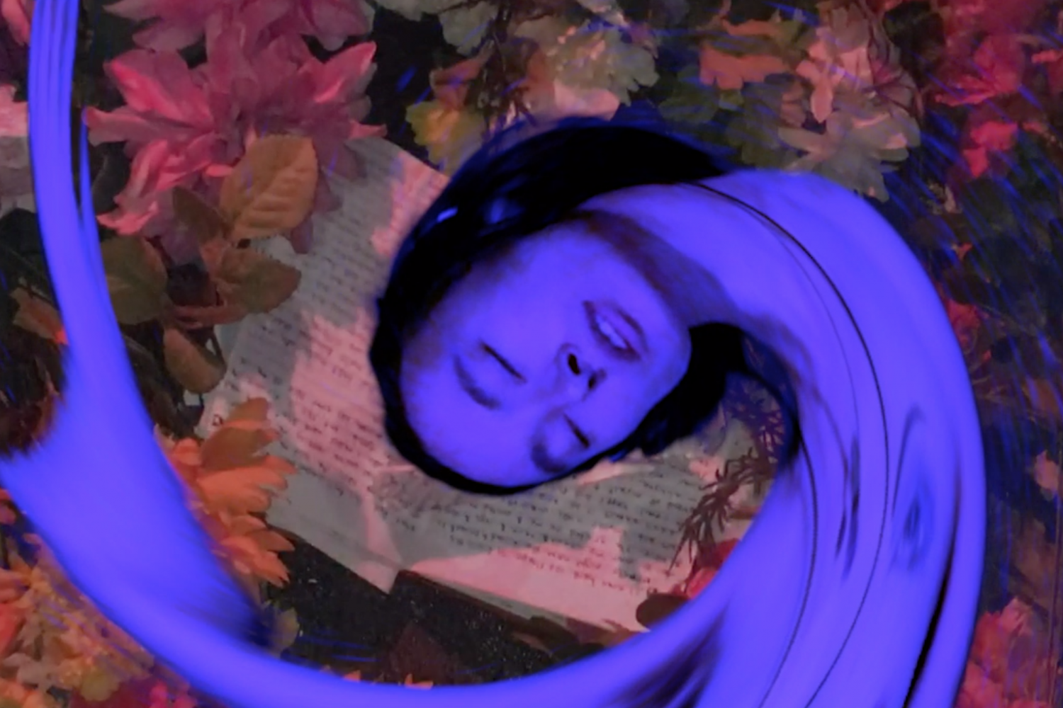 A still from a video by artist JK Chang/SLIPSTREAM. Superimposed on collage of an open journal and fall foliage, JK's face and upper torso are tinted purple, their eyes are closed, and they are stretched into a curlicue to resemble an elongated fish body.