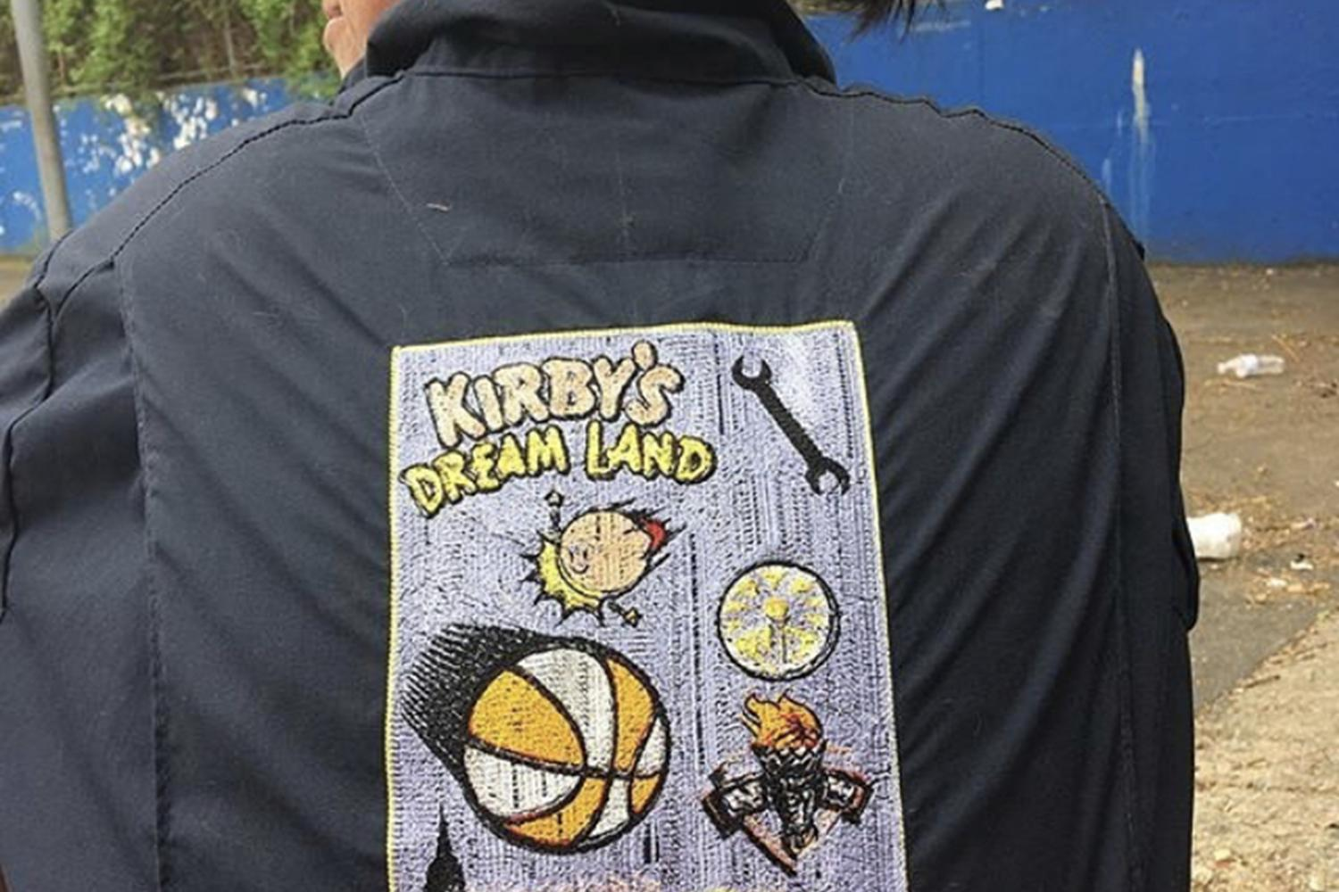 "Artist Kirby Reiko McKenzie faces away from the camera, looking over her left shoulder, dark hair pulled back in a low bun. Kirby wears a black jacket with a print on the back that depicts a basketball flying through the air and the words ""Kirby's Dream Land -- RAGE"""