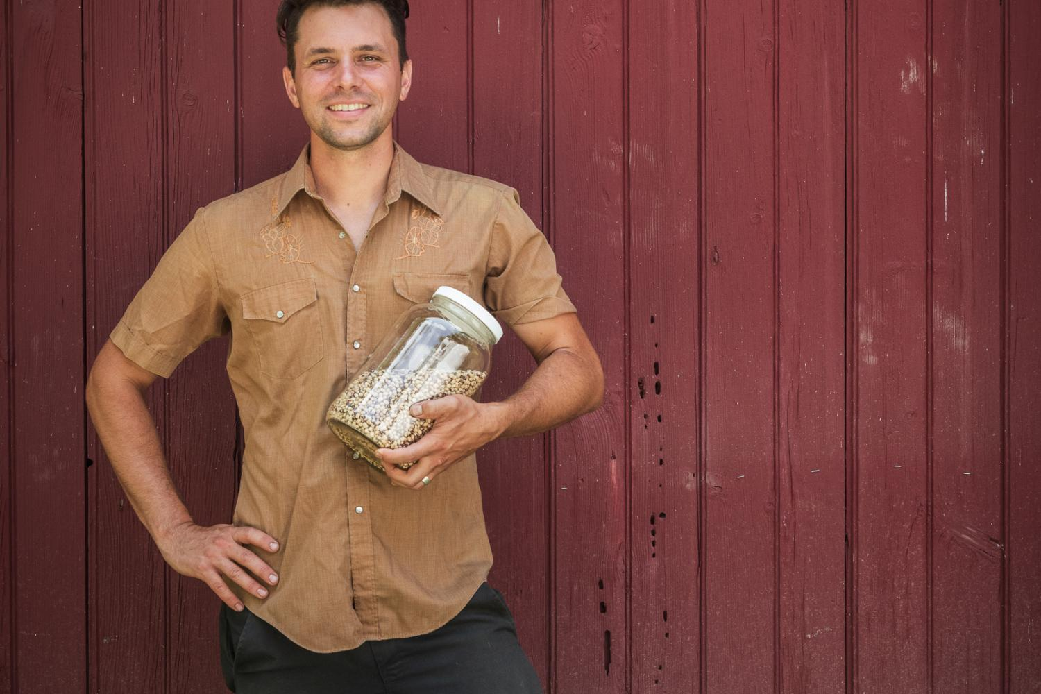 Artist Owen Taylor / TrueLove Seeds stands in front a deep red paneled wall, he wears dark denim work jeans and a short-sleeved workshirt. Owen leans to the side, one hand on his hip and the other balancing a clear mason jar filled with seeds. Owen smiles confidently at the camera.