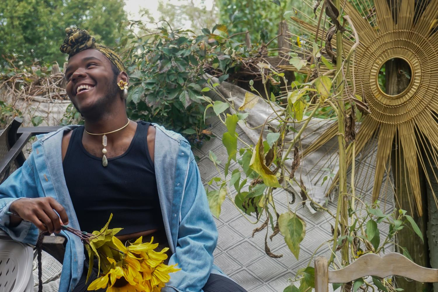 The Artist Vitche-boul Ra sits on an outdoor planter, laughing and holding s bunch of sunflowers. Ra is wearing a black jumpsuit, headscarf, light blue open jacket, and silver jewelry.