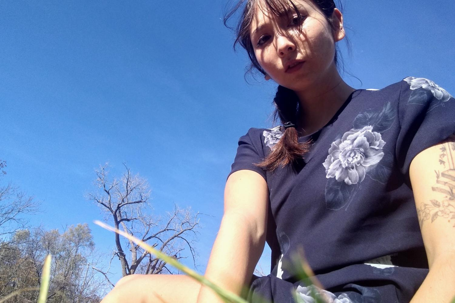 The artist Rachel Ishikawa sits in the grass outside against a clear blue sky. Her hair is a in a low braid over her shoulder, bangs falling in her face as she turns to look at the camera. She is wearing dark t-shirt dress with a floral design.