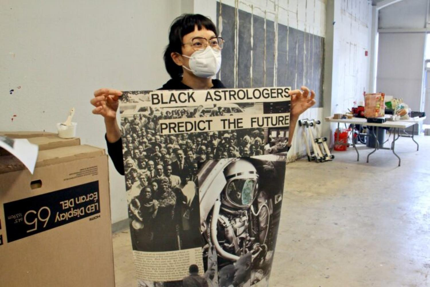 "AAI Executive Director Anne Ishii hold up a wheatpasting poster designed by Moor Mother, which features a black and white collage of astronomical figures and the text: ""Black astrologers predict the future"""