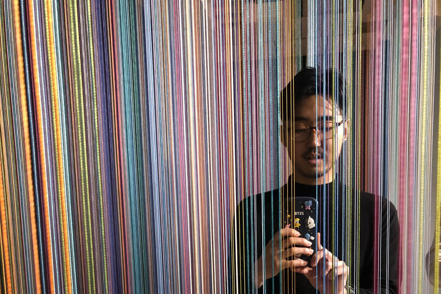 Man with black hair and glasses holding a camera and standing behind a screen of colorful long strands of string.