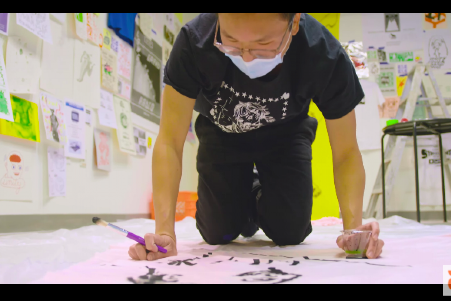 Videostill of the artist Jeff Cheung handpainting a banner on the ground