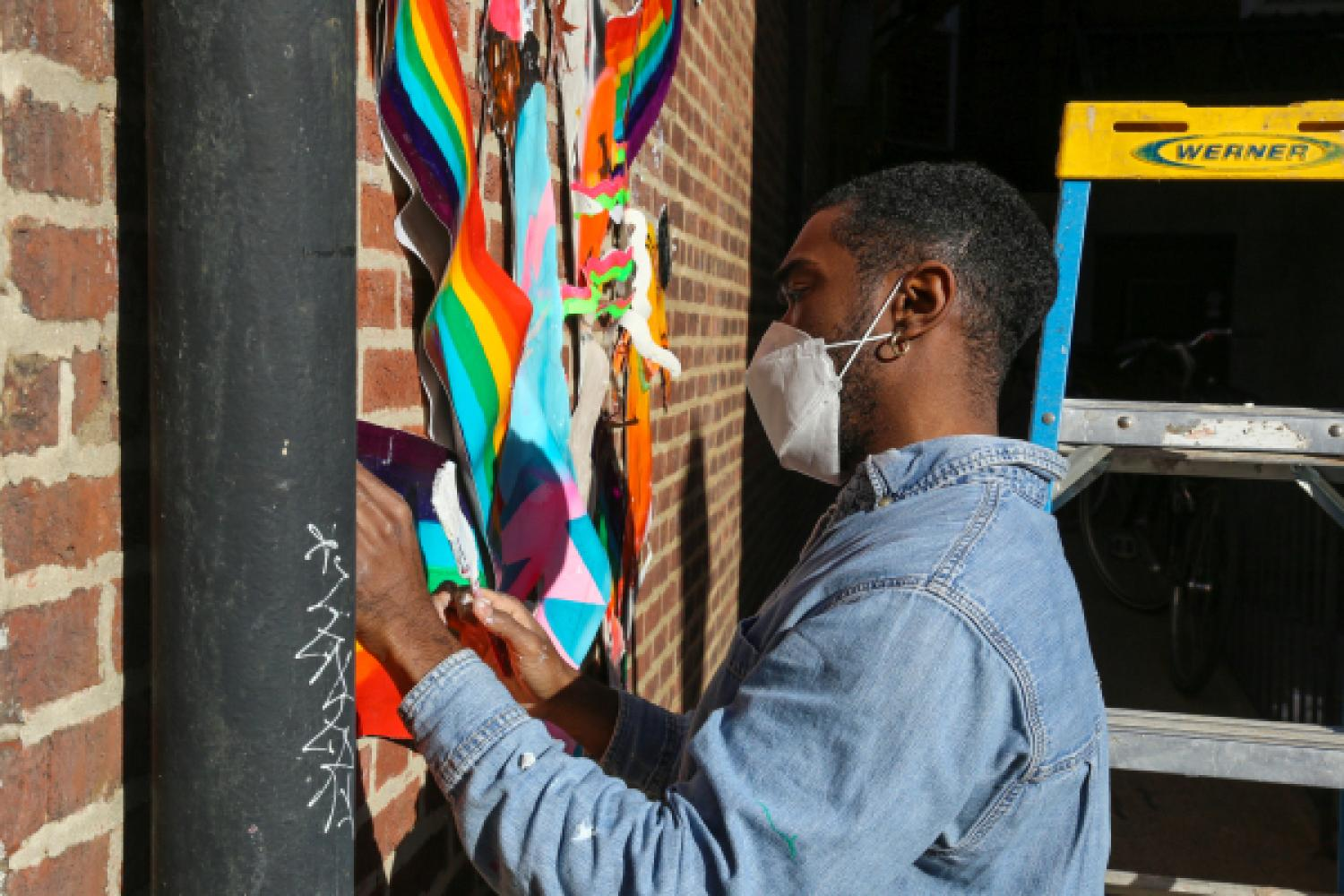 Artist Khari Johnson-Ricks pastes his mural to the side of The Attic Youth Center brick wall. Khari foregrounds a tall ladder and is weaing a denim chore coat and white facemask. The mural is dynamic and rainbow-colored against the brick.